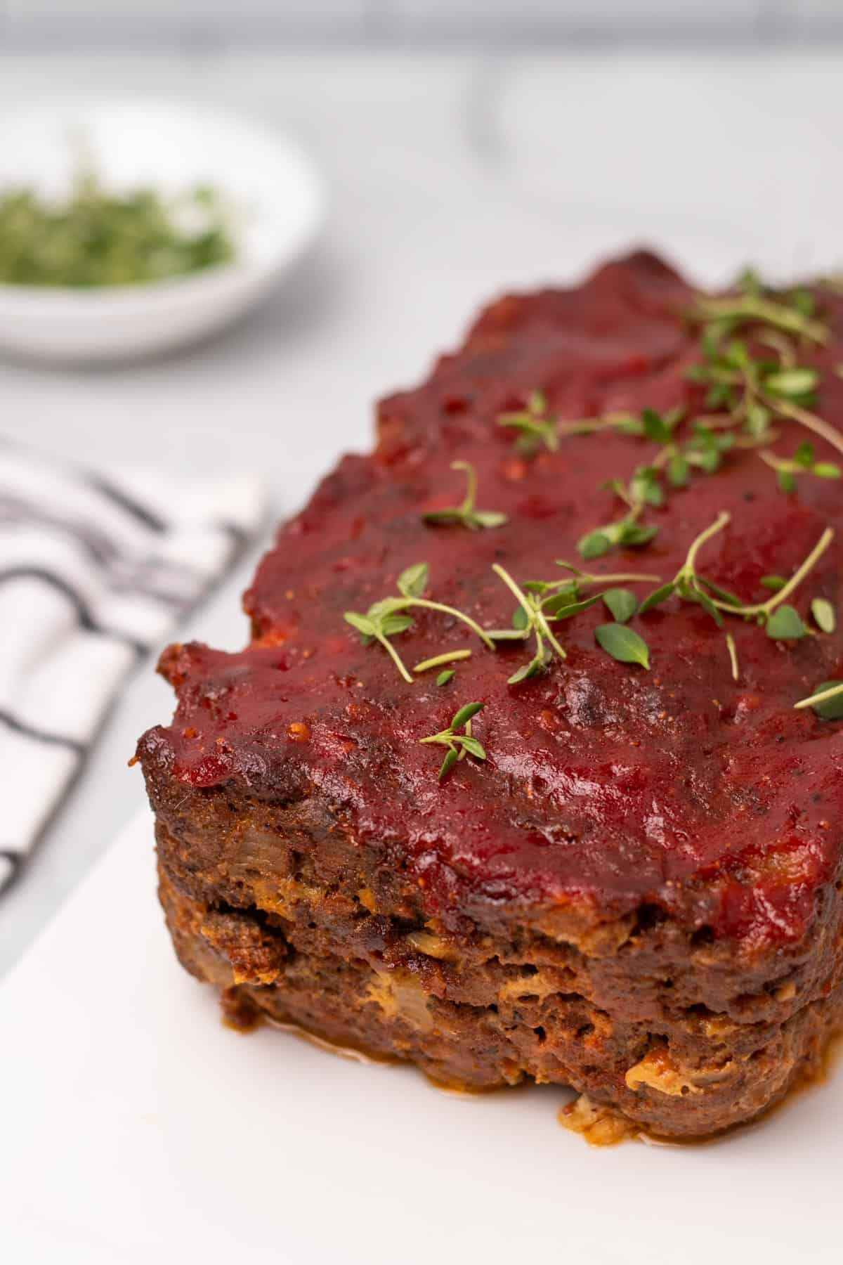 Keto Meatloaf with tomato topping and fresh thyme garnish on a white cutting board