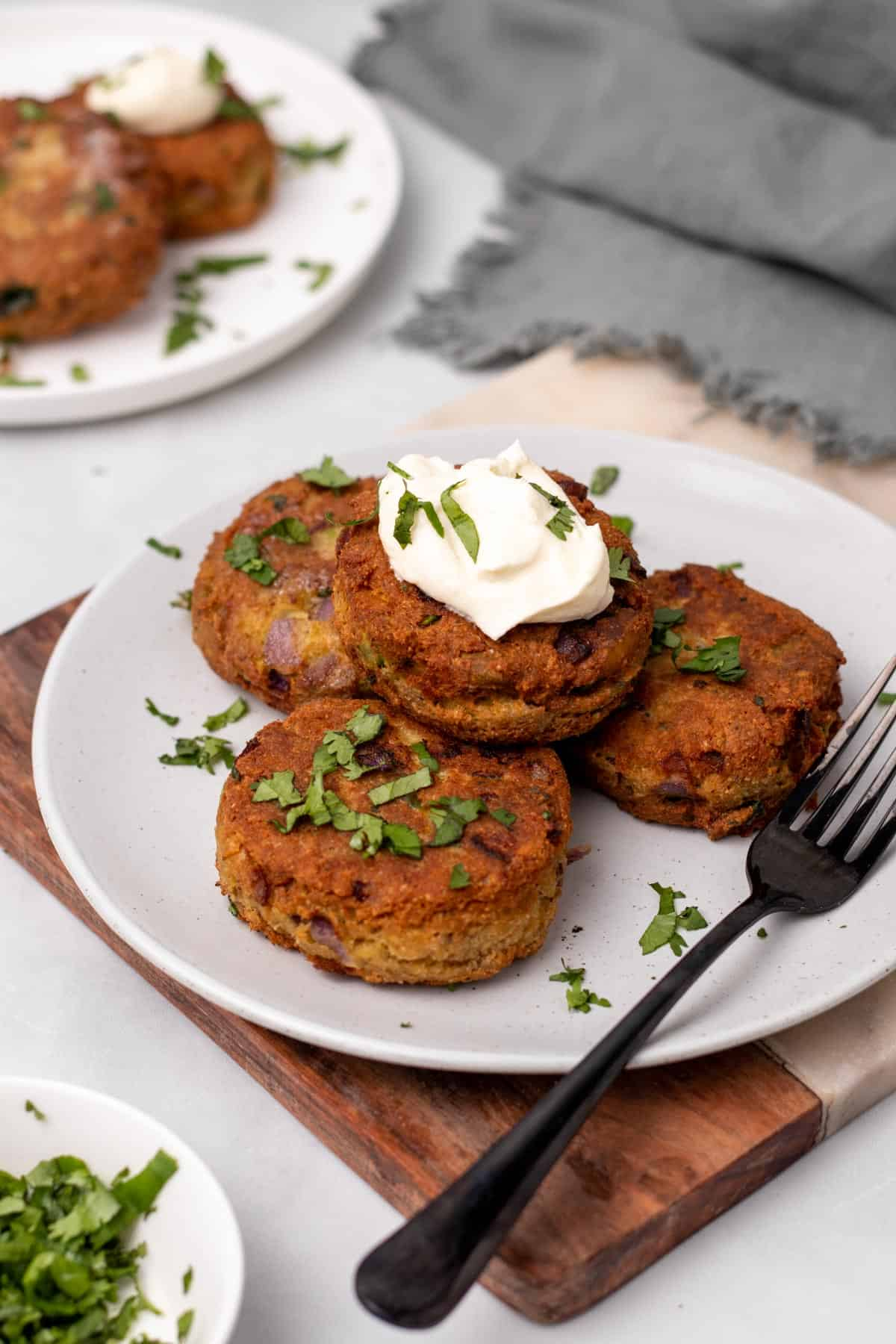 Four salmon patties on a white plate garnished with parsley and sour cream