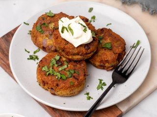 Keto salmon patties on a white plate garnished with parsley and sour cream