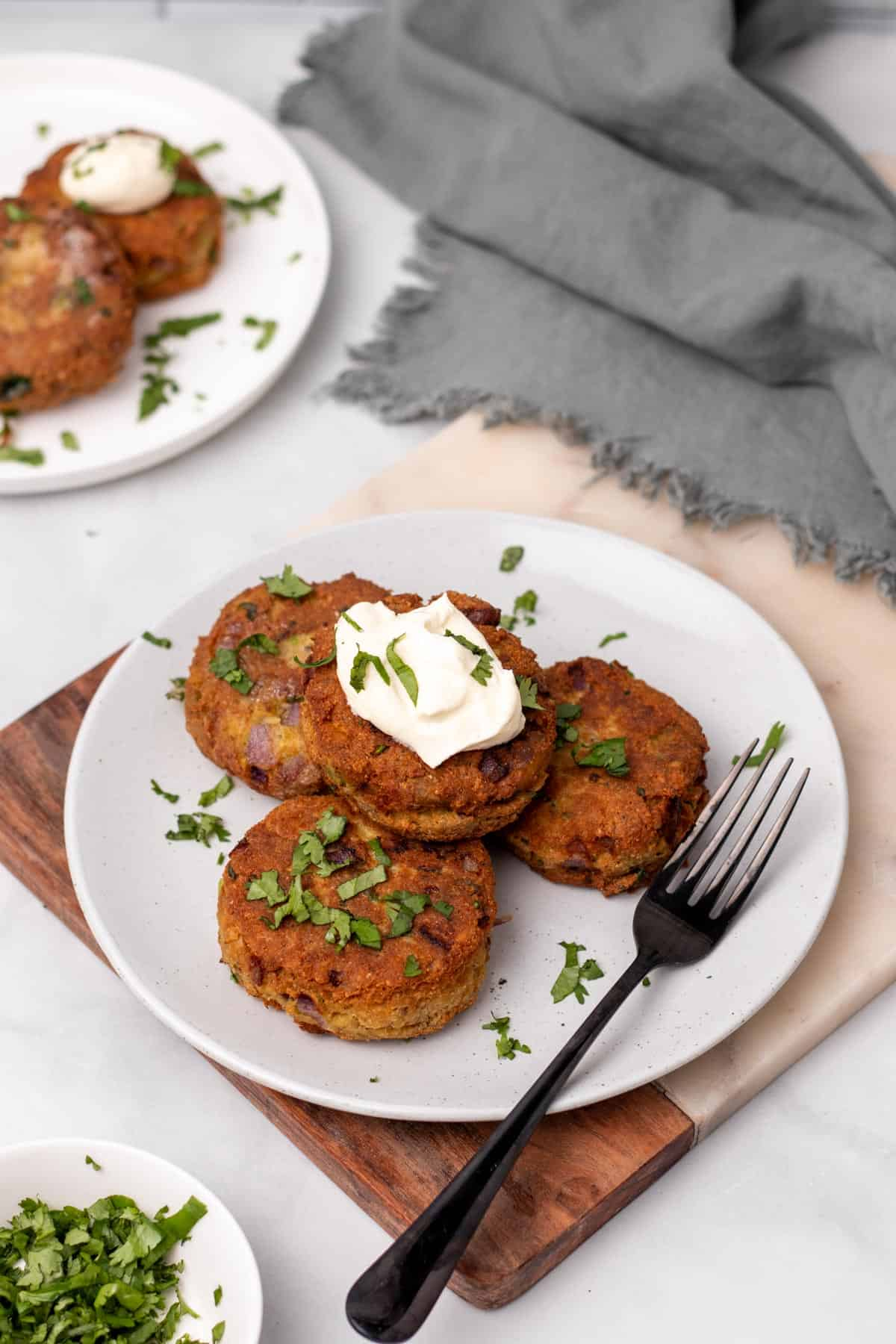Four keto salmon patties on a white plate with a fork, garnished with chopped parsley and a dollop of sour cream