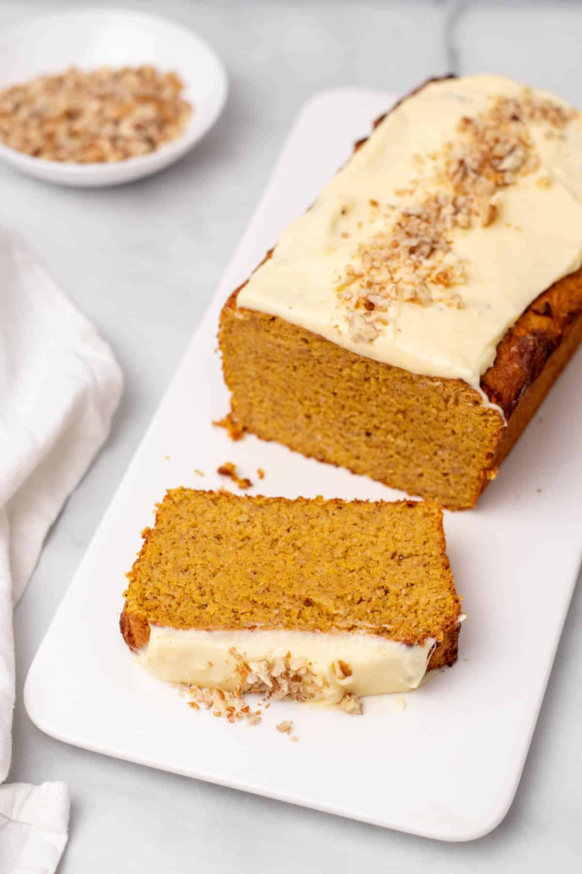 Pumpkin loaf on a serving tray with one slice in the foreground