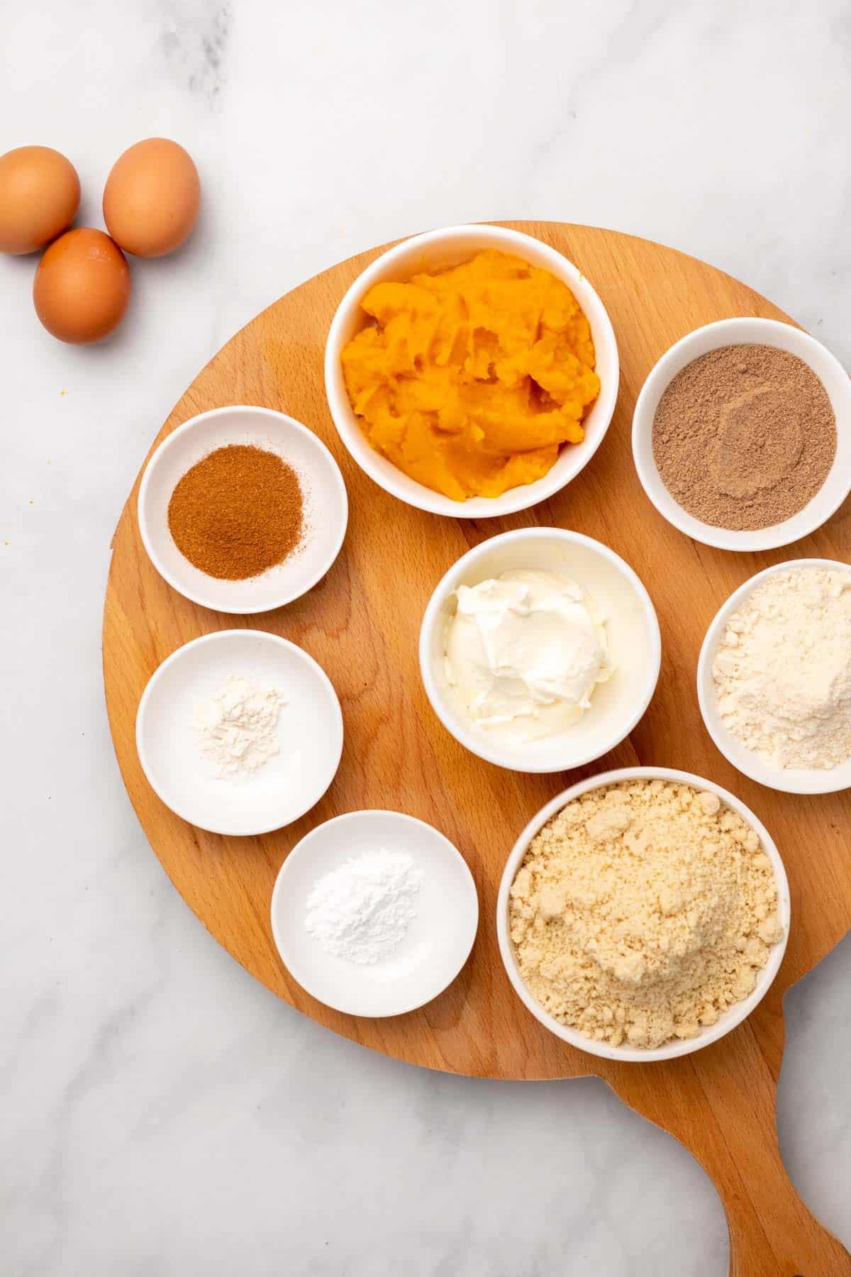 Pumpkin loaf ingredients in separate ramekins, as seen from above