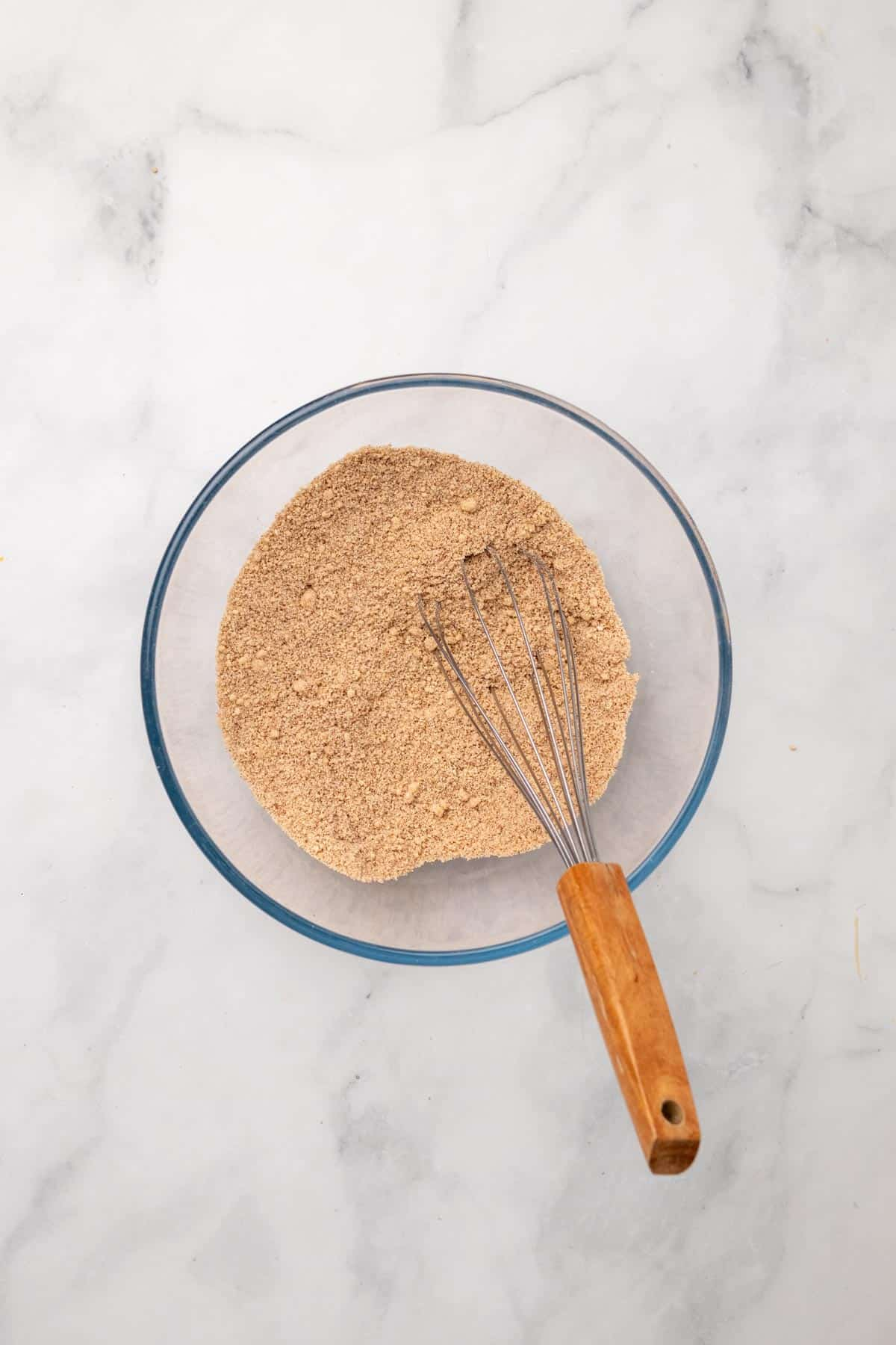 Dry ingredients in a glass bowl with a whisk