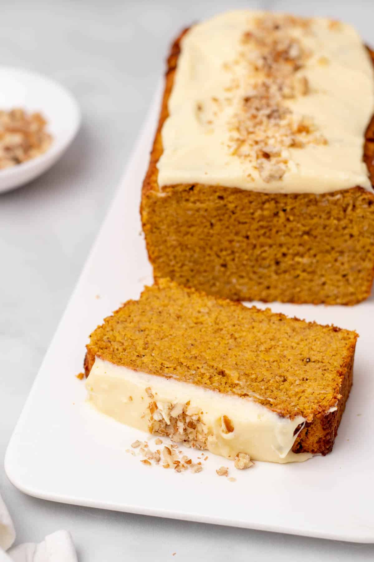 Keto pumpkin bread loaf on a white platter with one slice in the foreground