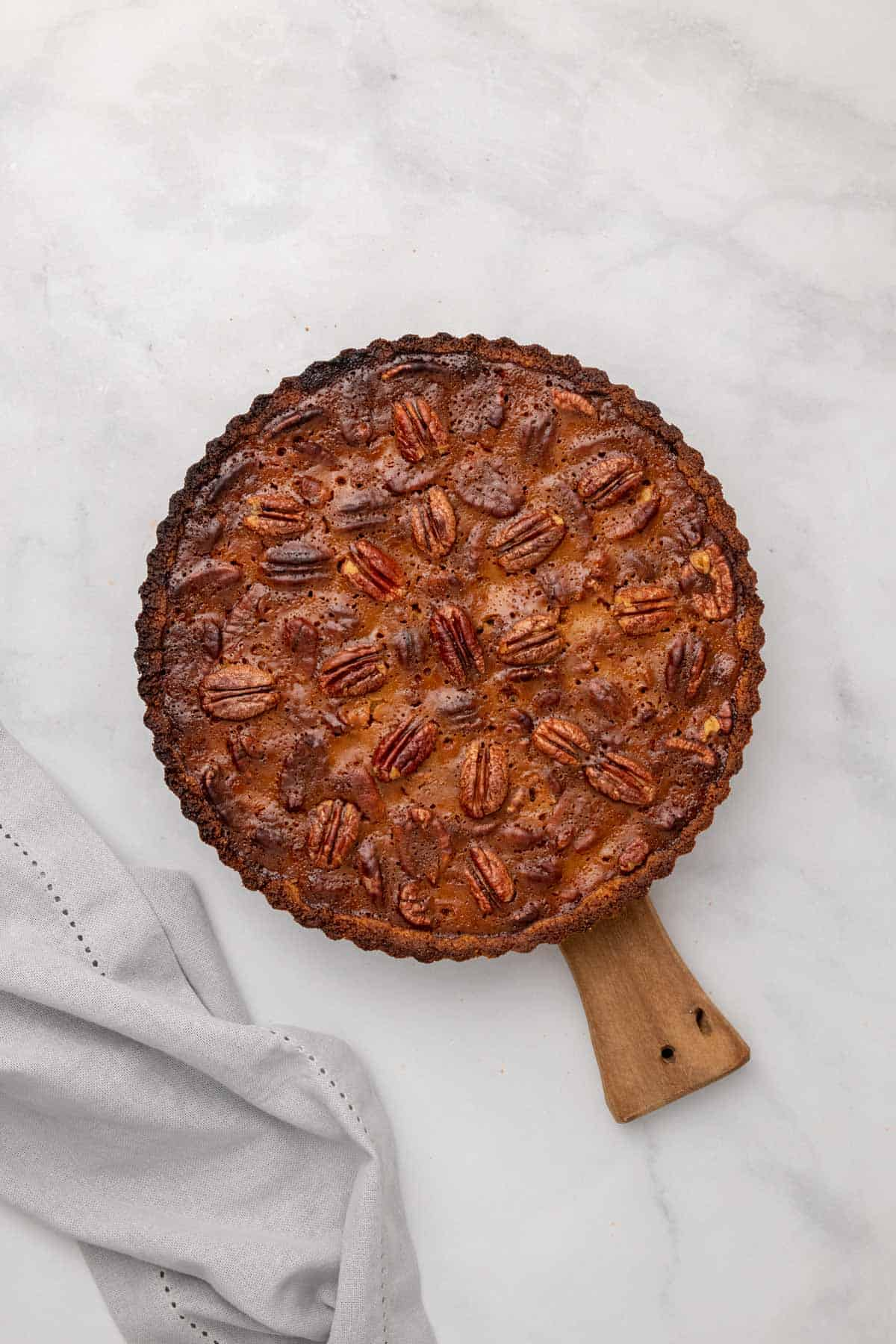 Baked pecan pie on a wooden serving board, as seen from above