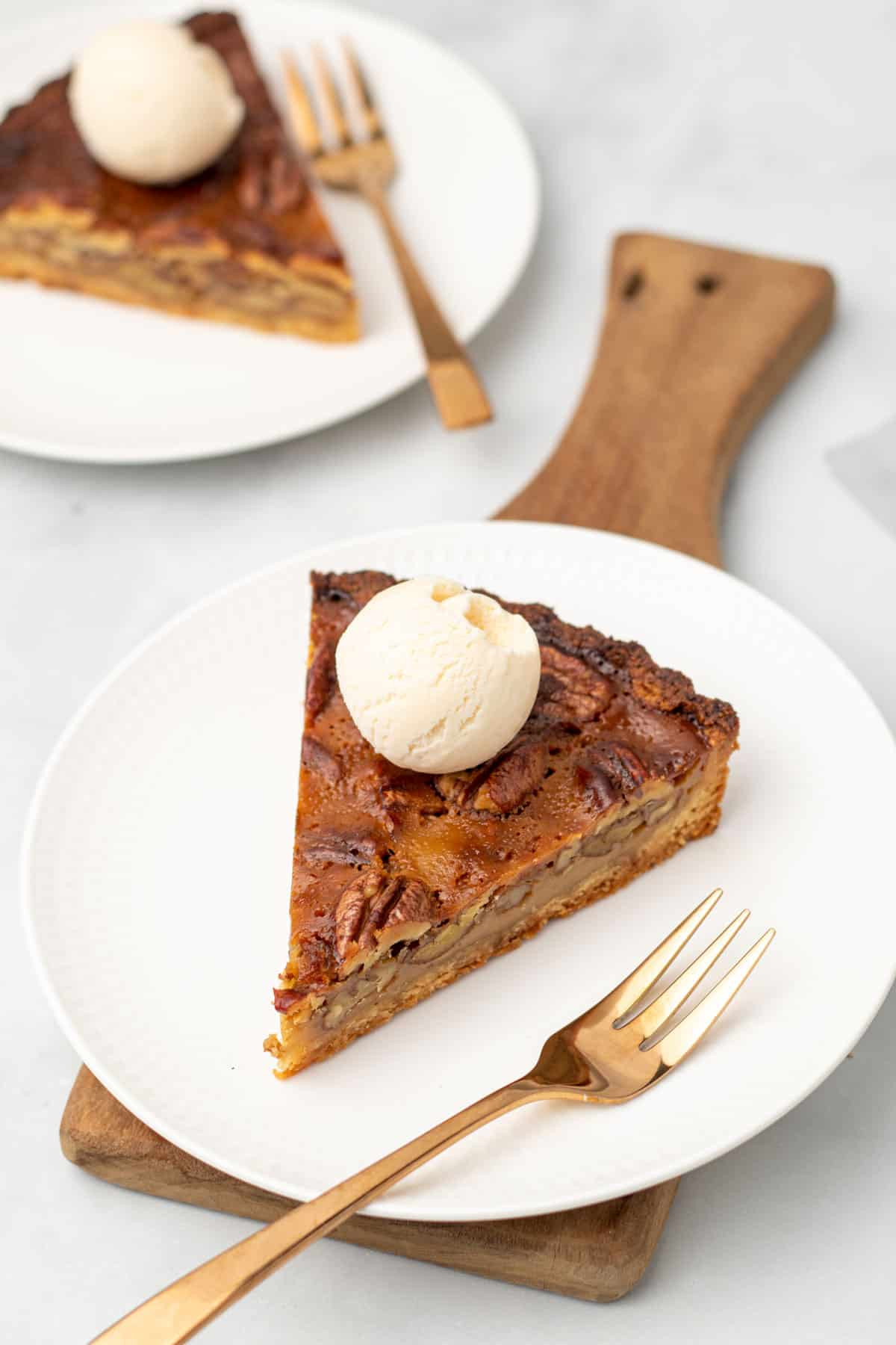 A slice of pecan pie on a plate with a scoop of vanilla ice cream on top next to a gold fork