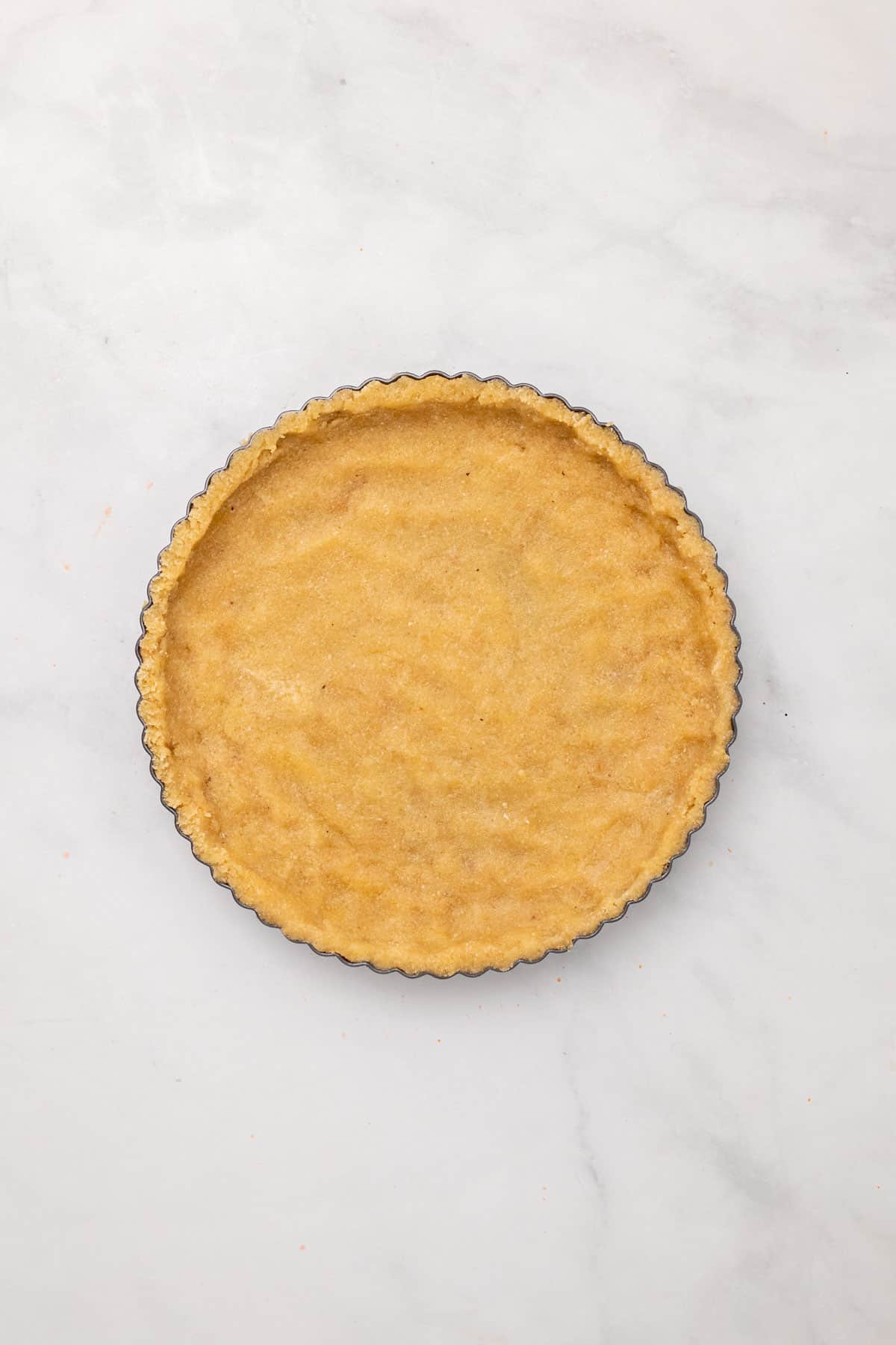 Pie crust pressed into a pie pan, as seen from above
