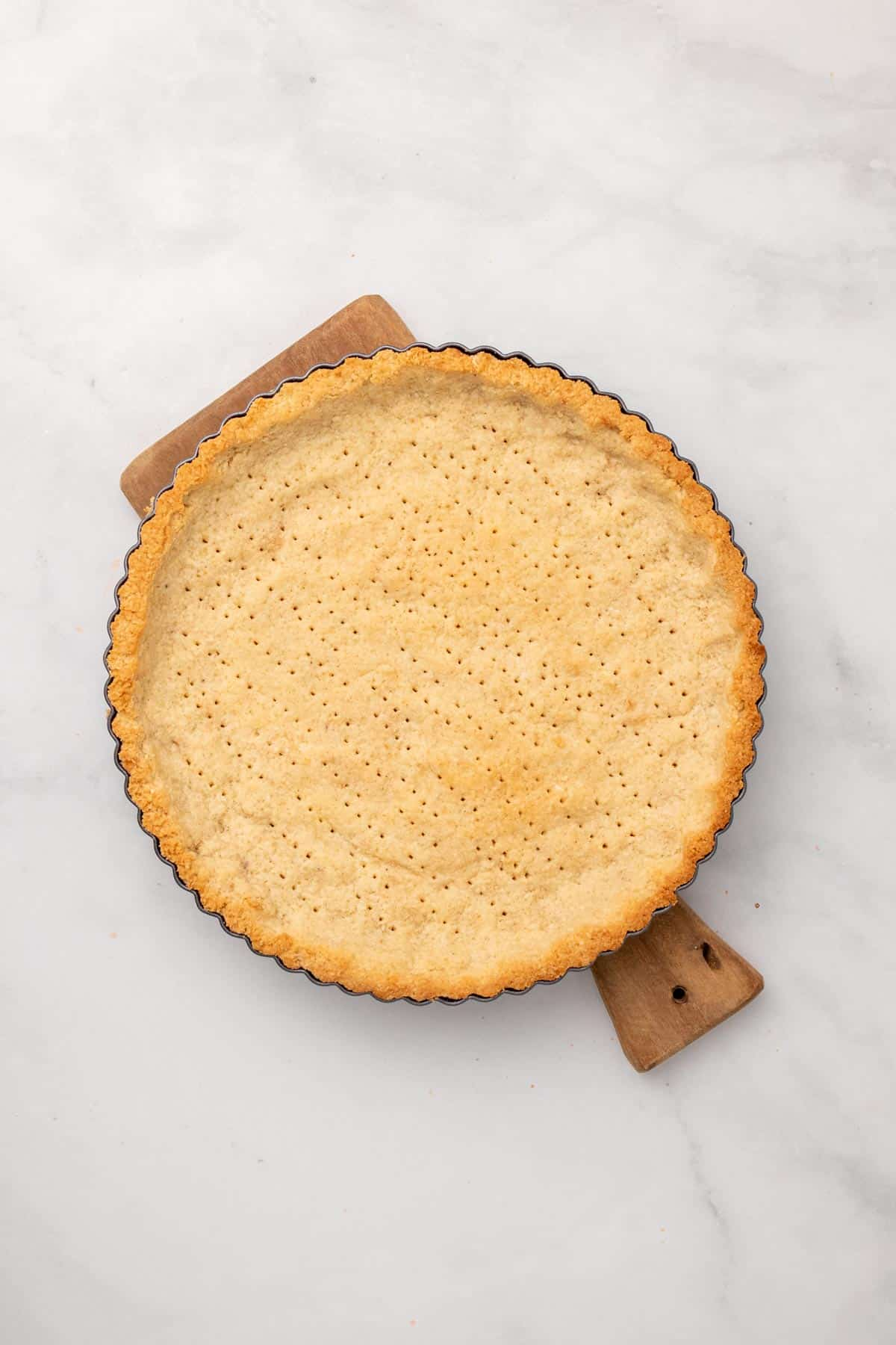 Baked pie crust in pie dish poked full of holes