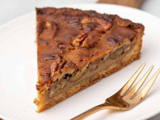 Slice of pecan pie on plate with fork