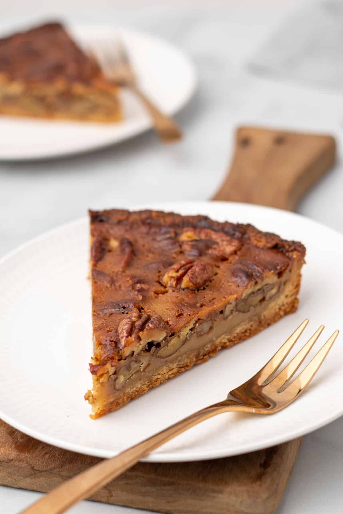 A slice of low carb pecan pie on a white plate with a gold fork, as seen from the side