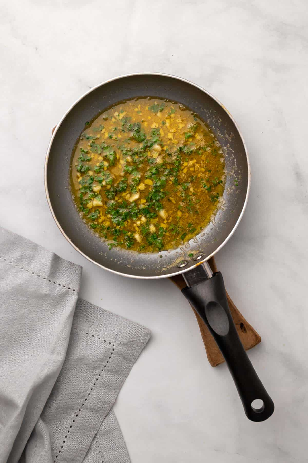 Garlic, butter, parmesan, and chopped parsley in a small saucepan, as seen from above