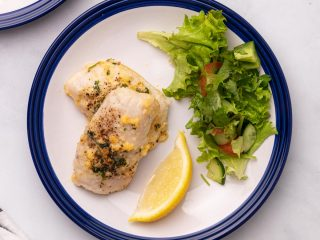 Cod plated with a lemon wedge and salad