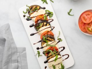 Caprese salad with eggplant on a white serving dish, as seen from above
