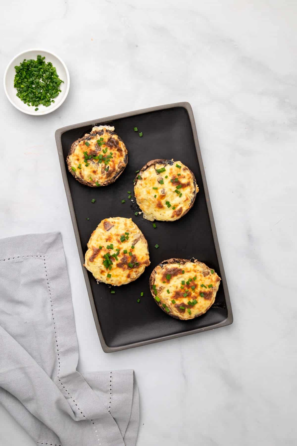 Overhead view of baked mushrooms stuffed with cheese on a baking tray next to a ramekin of fresh chives