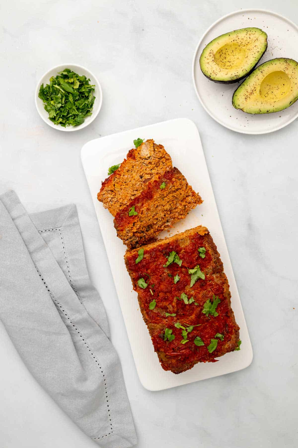 Taco meatloaf on a serving platter with 2 slices cut next to a ramekin of cilantro and avocado halves on a plate