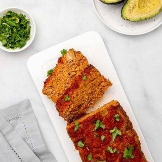 Taco meatloaf on a white serving platter with two slices cut from the loaf
