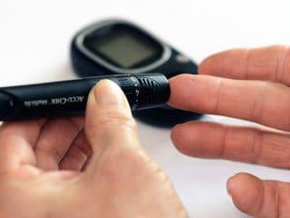 Hands of person measuring blood sugar