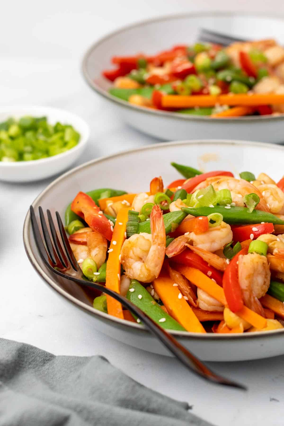 Close-up of stir fry in a white bowl with a fork