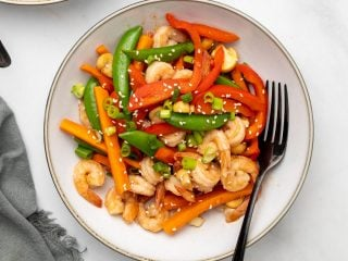 Keto shrimp stir fry in a white bowl with a spoon