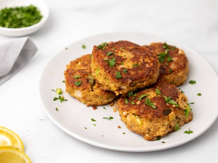 Four Low-Carb Crab Cakes on a white plate garnished with chopped parsley