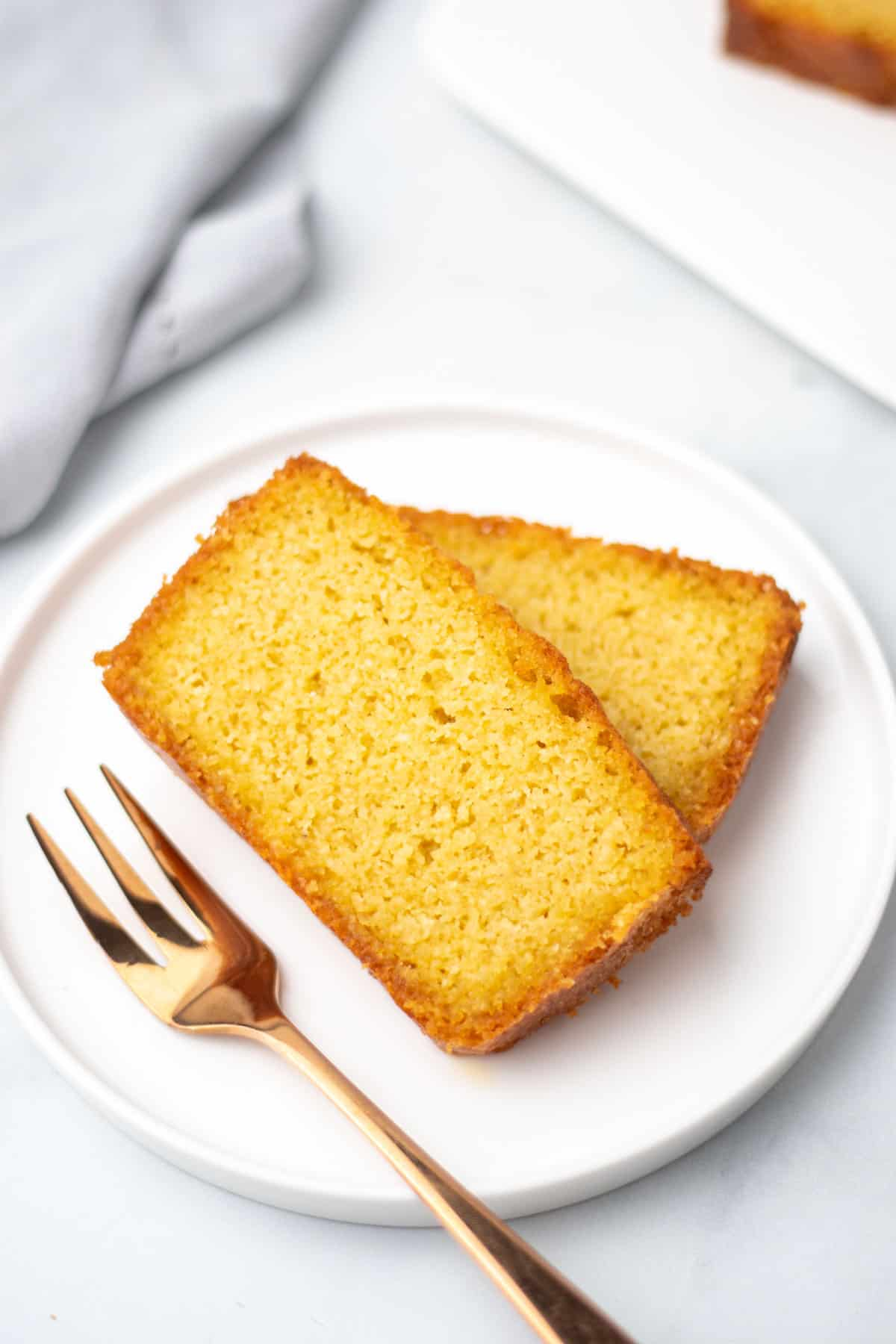 Two slices of pound cake on a white plate next to a fork