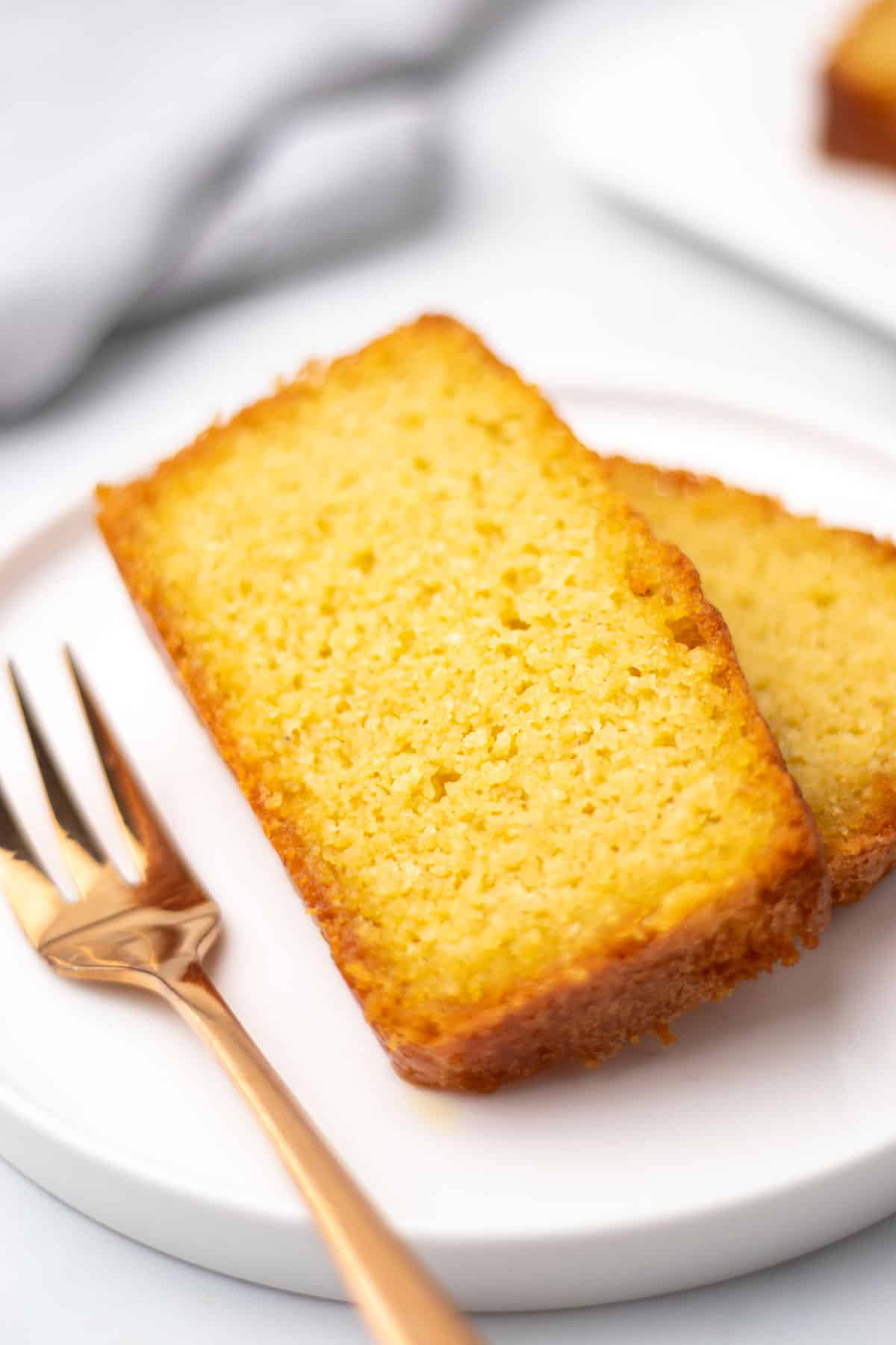 Close-up of two slices of pound cake of a white plate with a fork