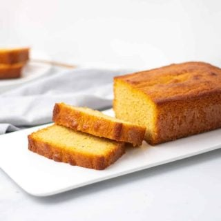 Low-Carb pound cake loaf on a white serving tray with two slices cut