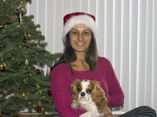 Christel sitting with dog in front of Christmas tree