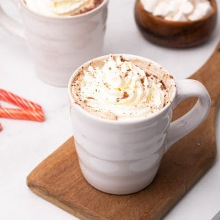 Skinny peppermint mocha latte topped with whipped cream on a wooden serving board