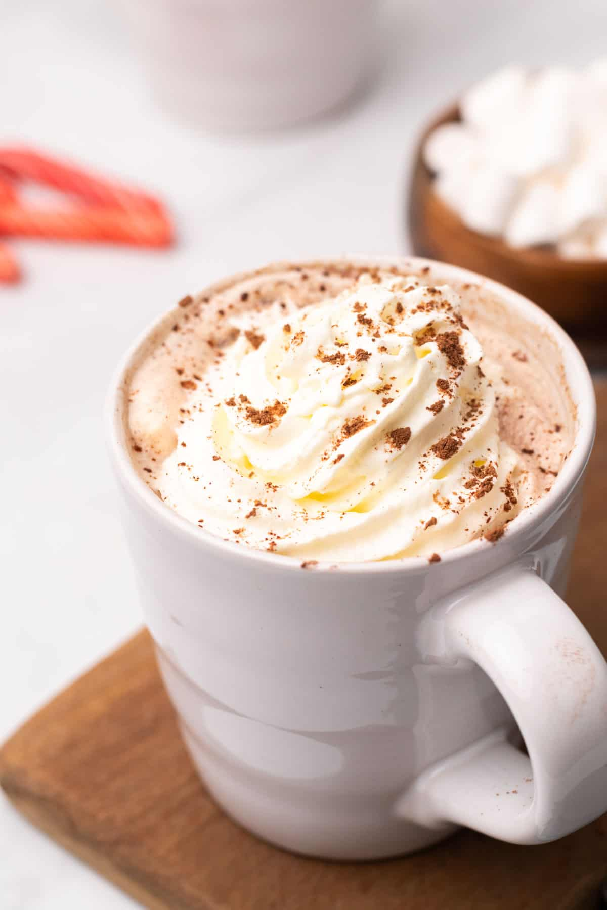 Latte in a white coffee mug topped with whipped cream