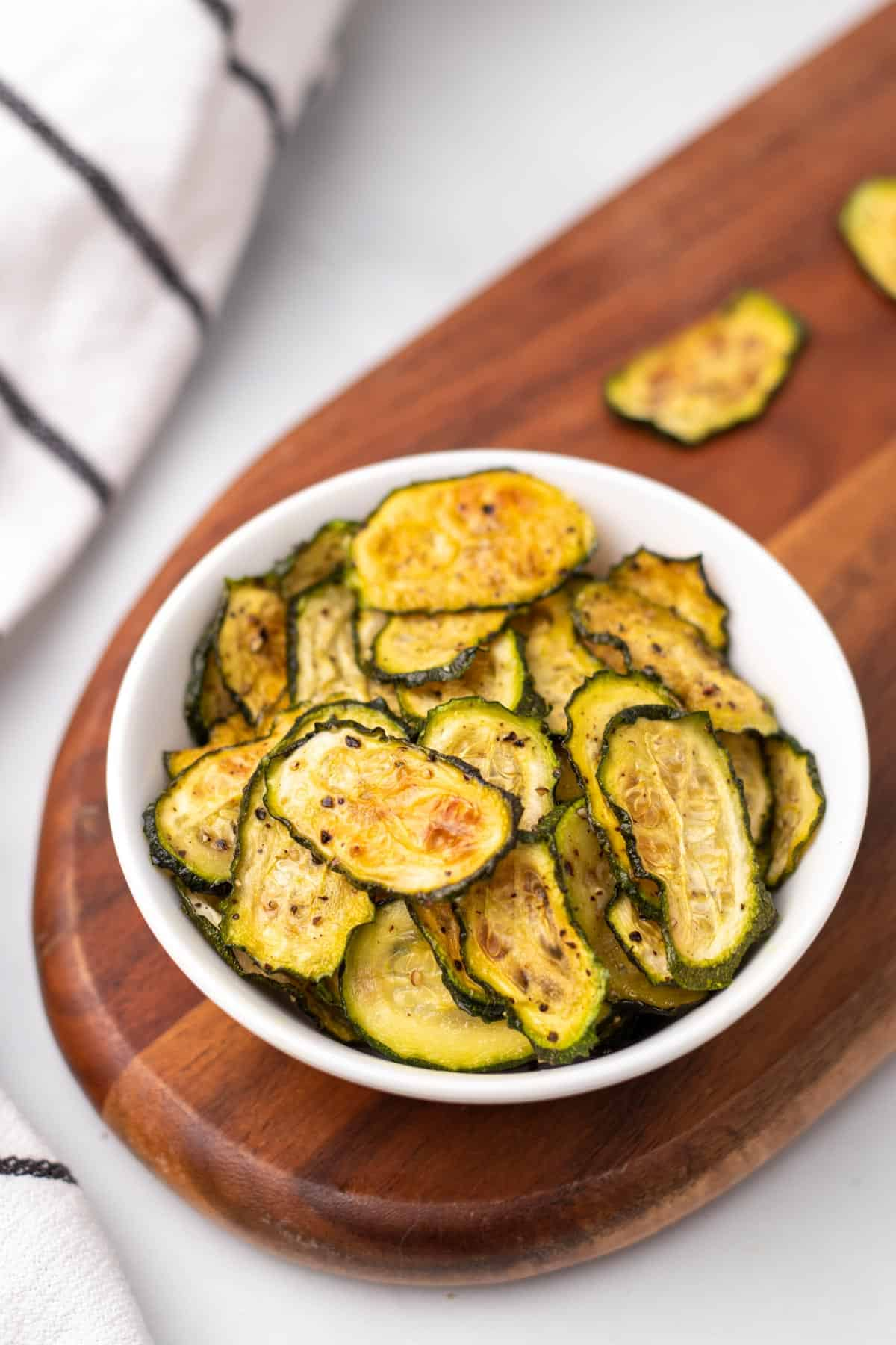 Bowl of baked zucchini chips on wooden board