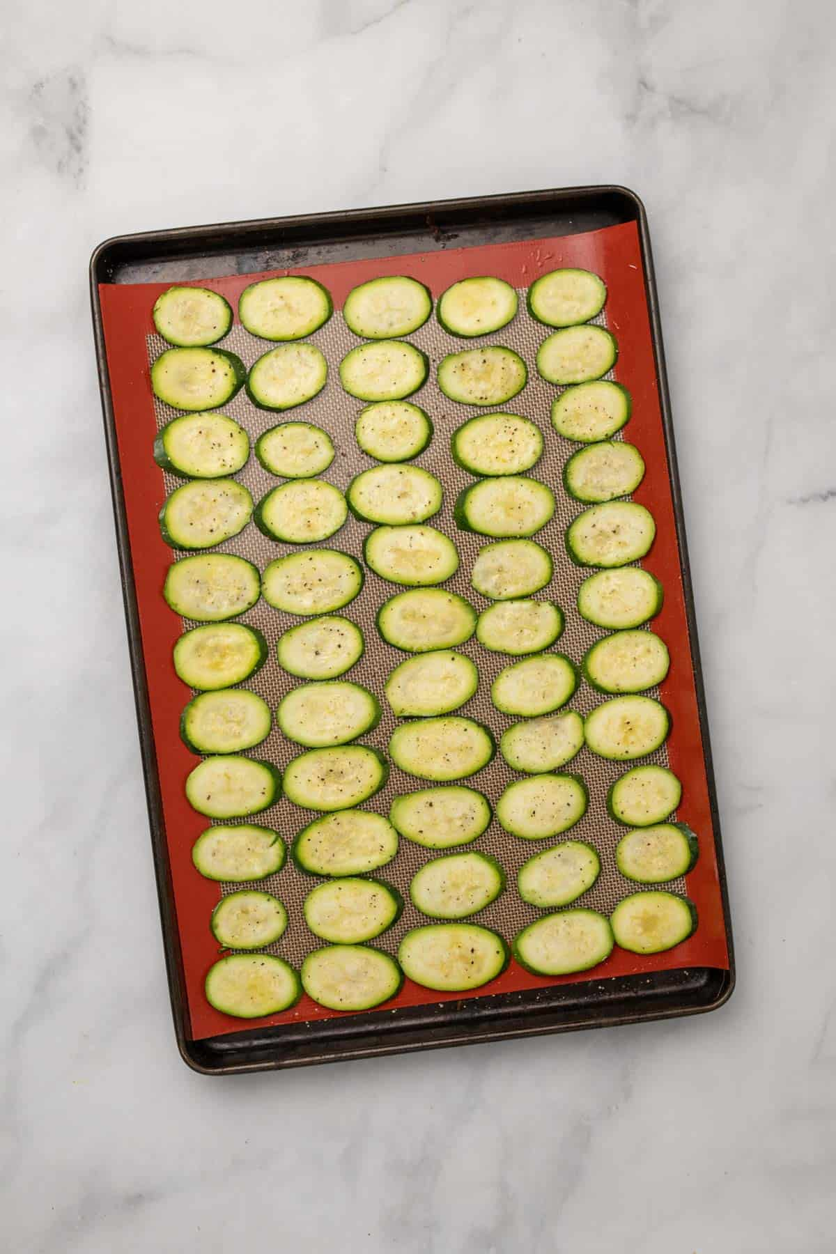 Seasoned zucchini slices on silicone baking mat