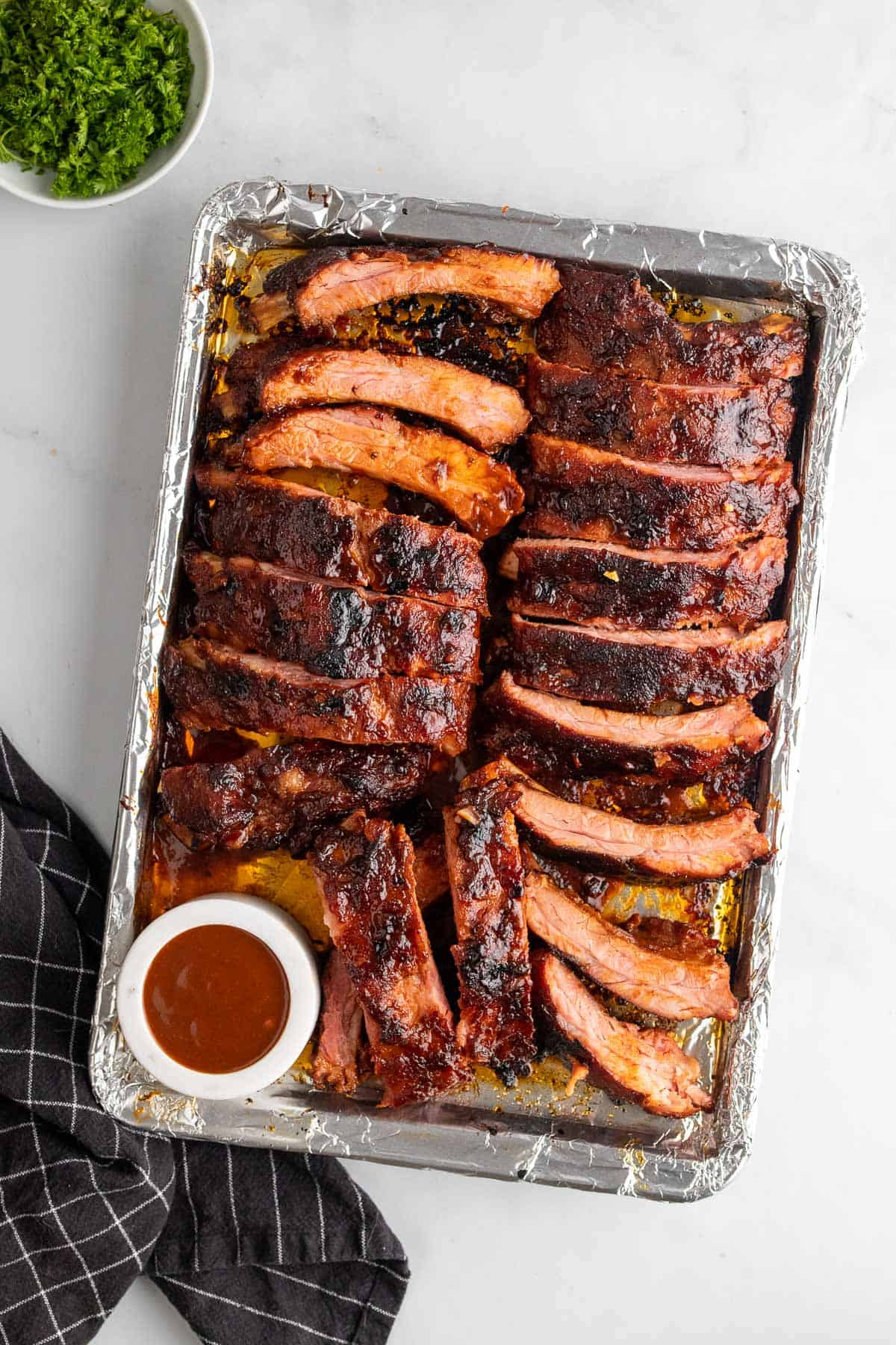 Sliced ribs on a baking sheet with a ramekin of barbeque sauce