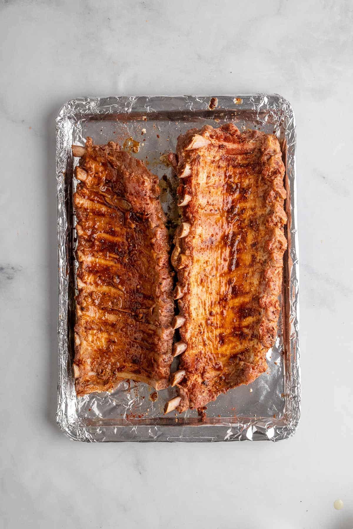 Two racks of ribs upside-down on a baking sheet