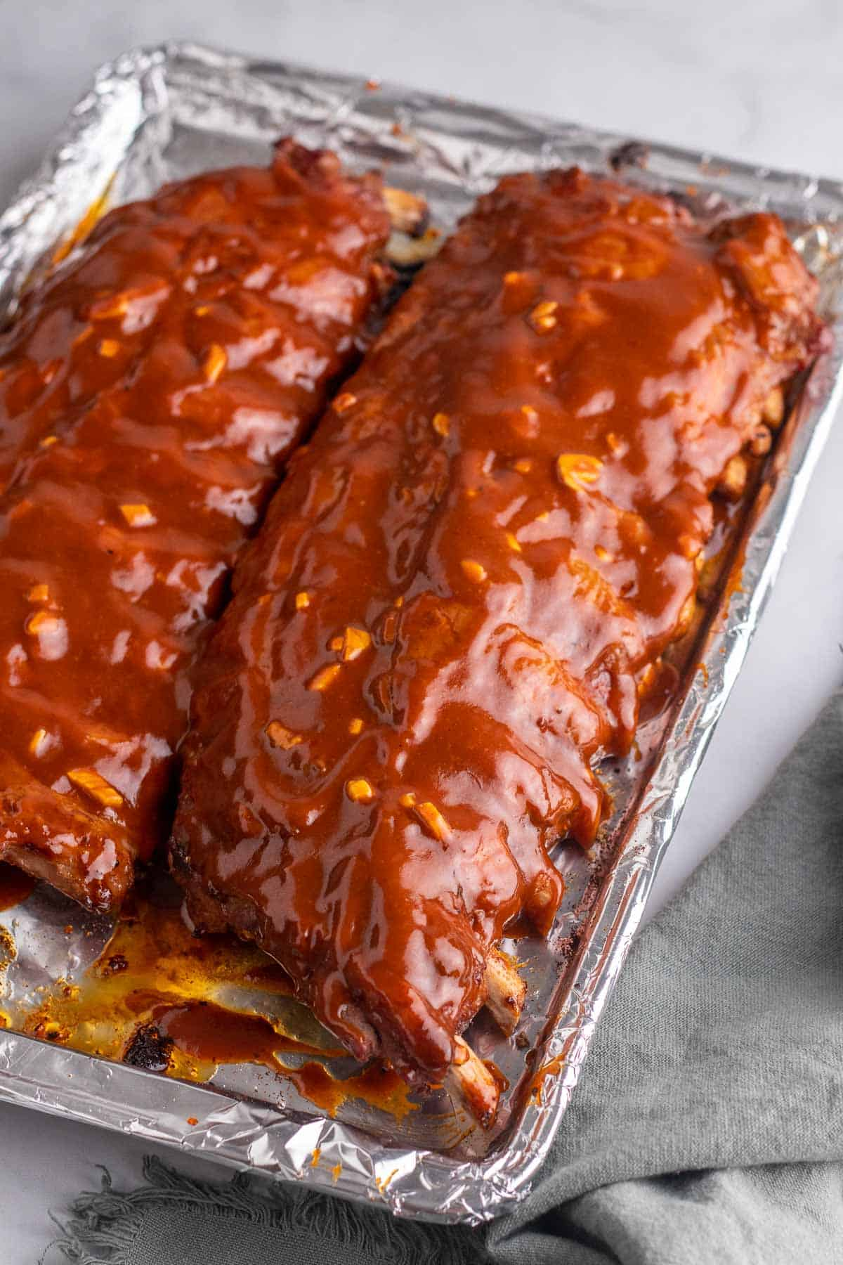 Two racks of ribs basted with barbeque sauce on a baking tray