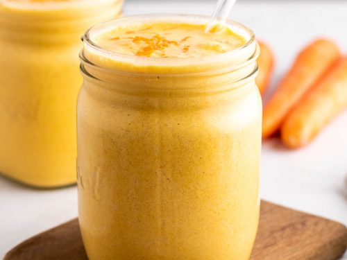 Carrot smoothie in a small glass mug with a glass straw on top of a wooden serving tray