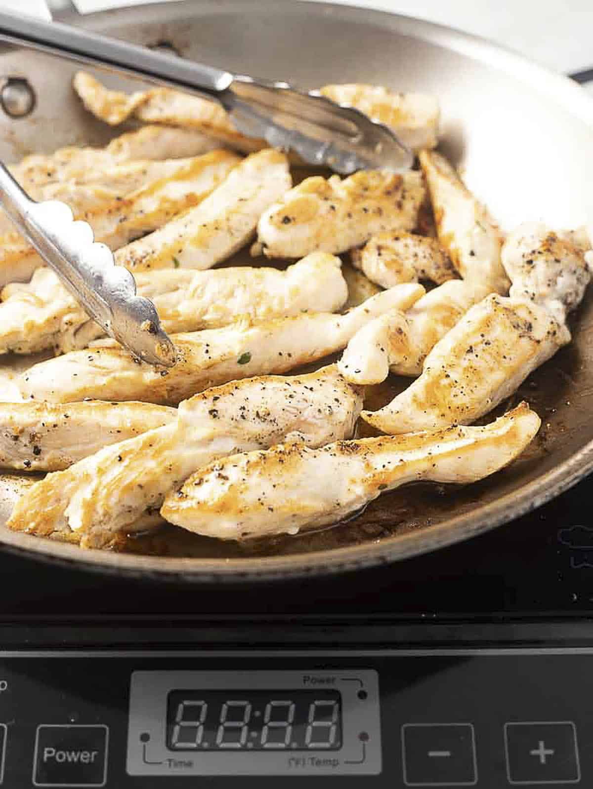 Sautéed chicken breast strips in a pan.