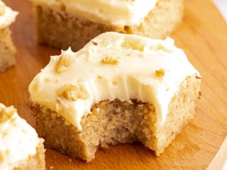 Keto spice cake cut into squares on a serving tray with a bite taken out of one square