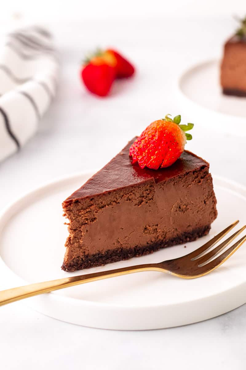 Low carb chocolate cheesecake slice on a white plate next to a gold fork, topped with a sliced strawberry