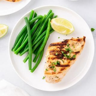 Yogurt marinated chicken breast on a white plate with steamed green beans and a wedge of lemon