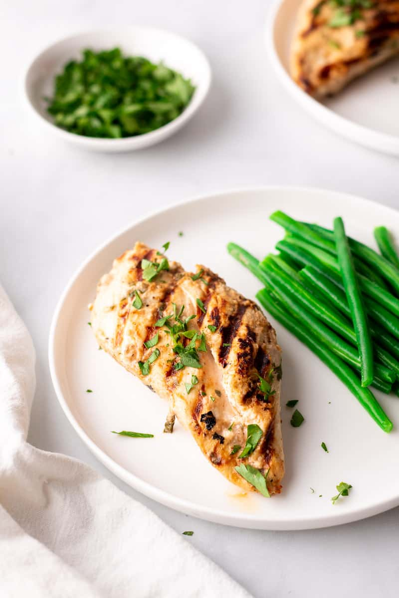 Chicken on a white plate with steamed green beans, garnished with fresh parsley