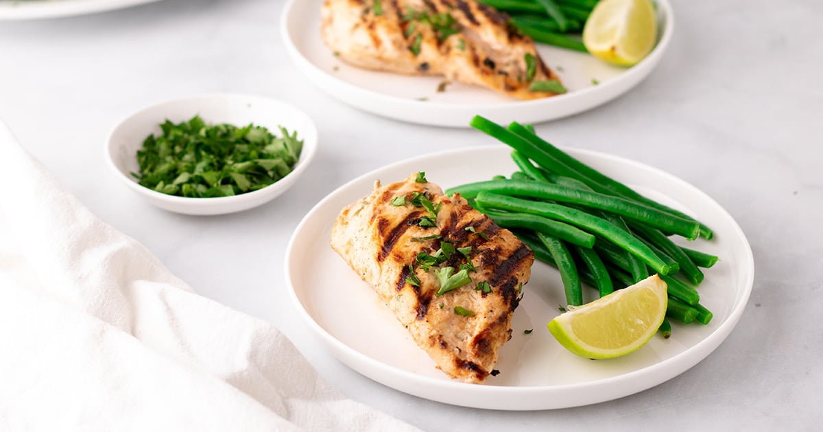 Closeup of a plate of chicken with steamed green beans and a lemon wedge