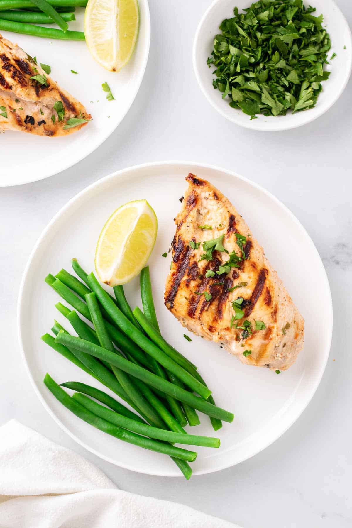 Overhead view of yogurt marinated chicken breast on a white plate with steamed green beans and a lemon wedge next to a ramekin of parsley