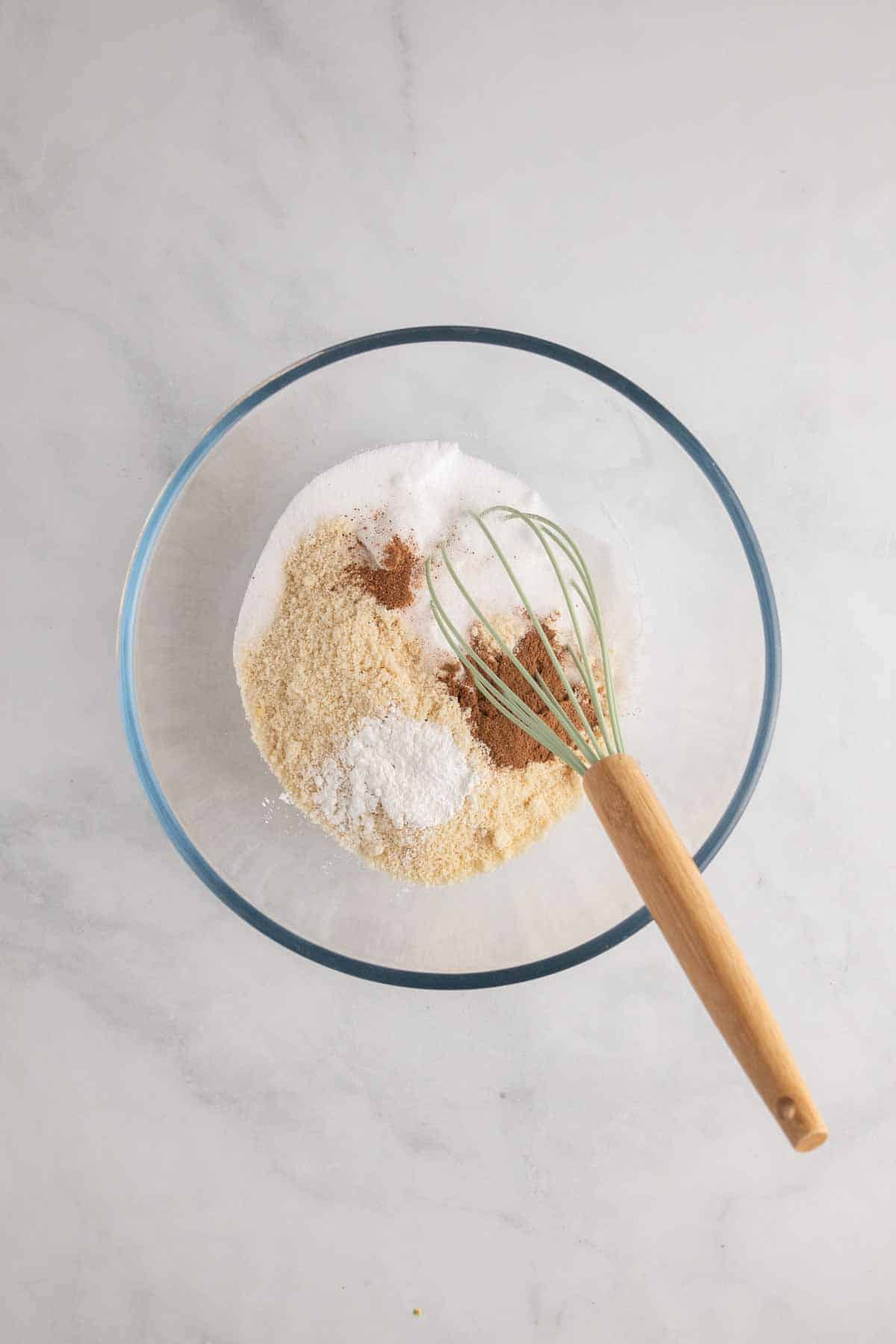 Dry ingredients in a glass bowl with a whisk, as seen from above