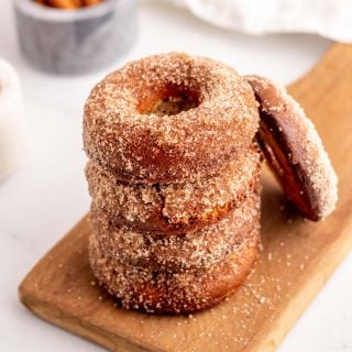 A stack of 4 cinnamon and sugar Keto donuts with a 5th donut leaning against the stack