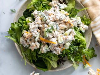 Keto chicken salad over fresh greens on a rustic plate, as seen from above