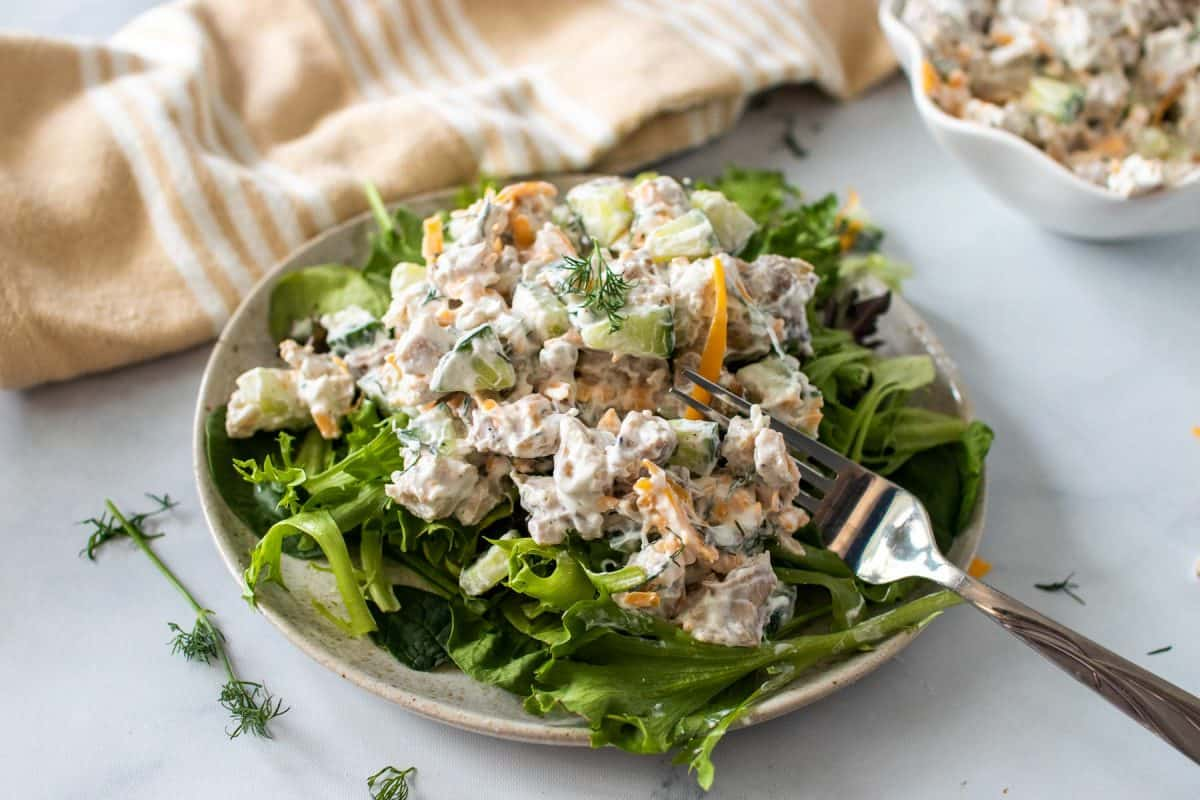 Chicken salad over fresh greens on a rustic plate with a fork