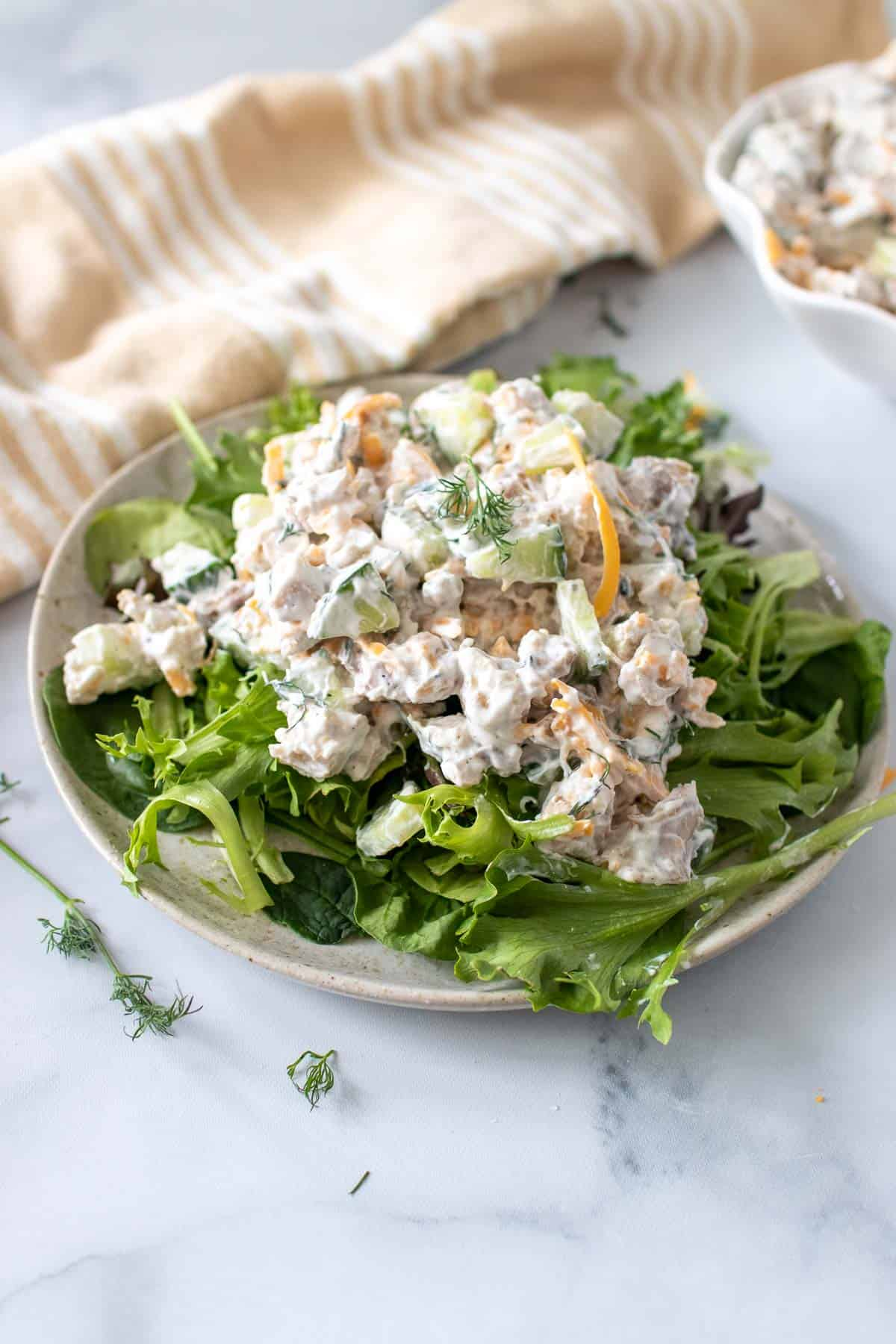 Chicken salad over fresh greens on a rustic plate with cloth napkin in the background