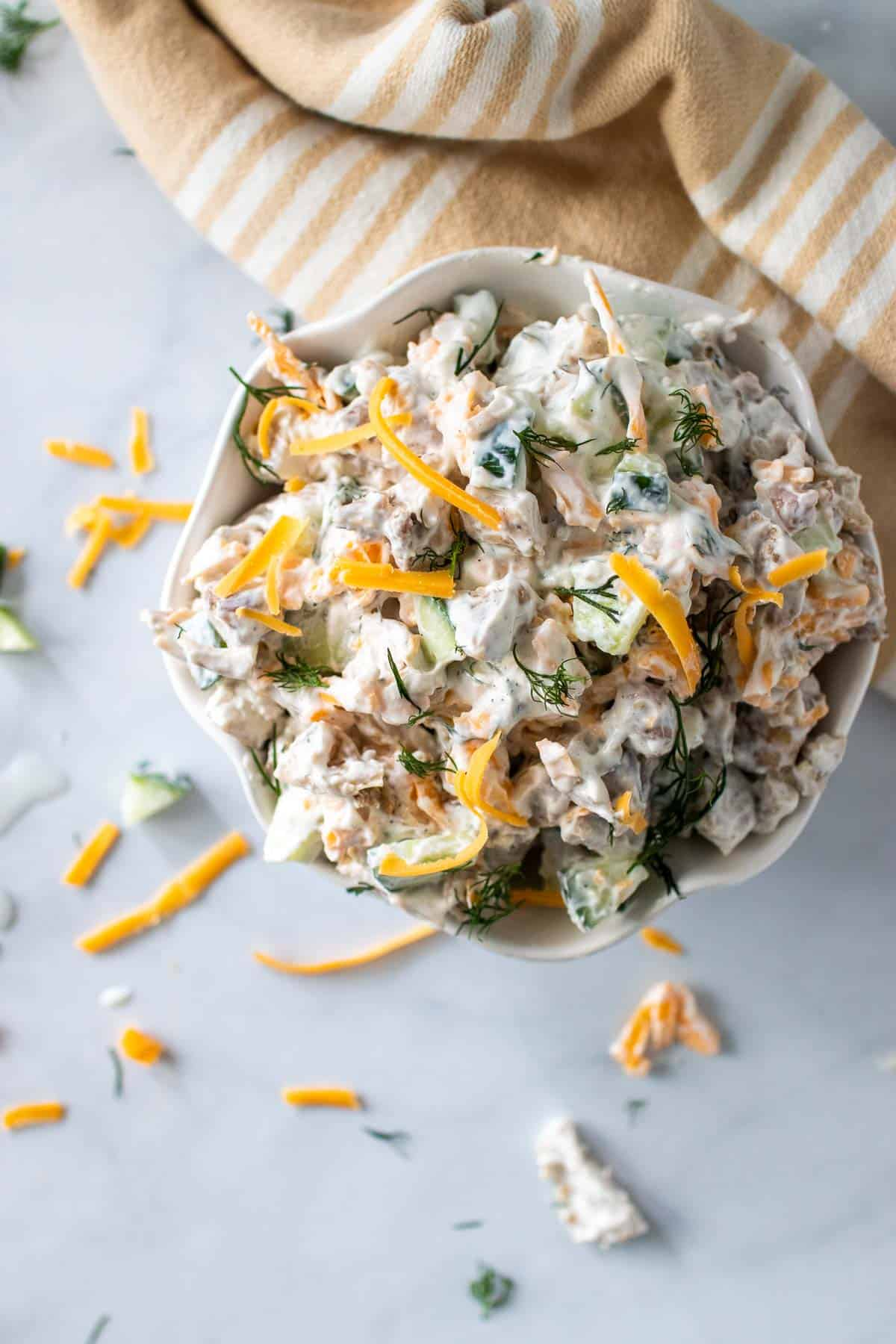 Bowl of chicken salad topped with shredded cheddar and fresh dill, as seen from above