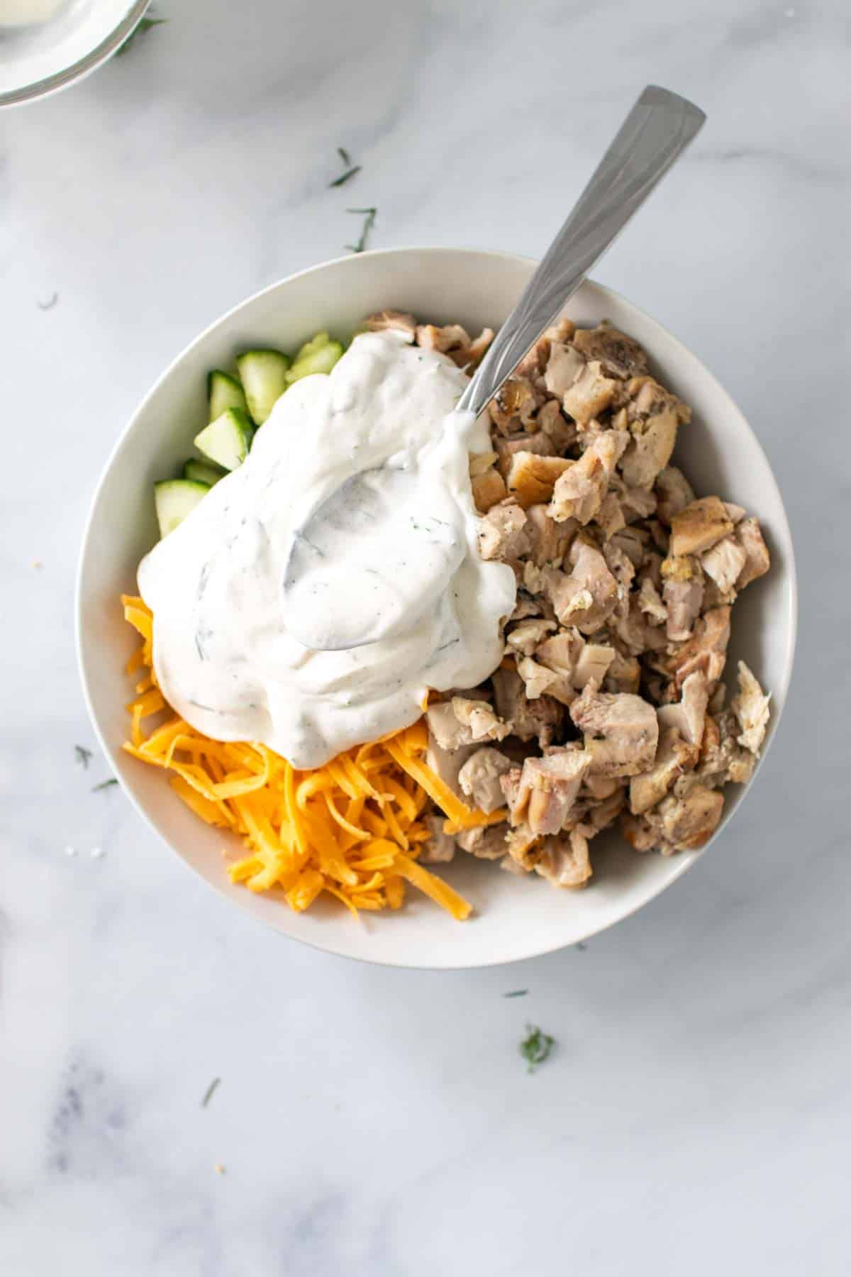 Greek yogurt mixture added to bowl of chicken thighs, cheddar, and cucumbers with a spoon, as seen from above